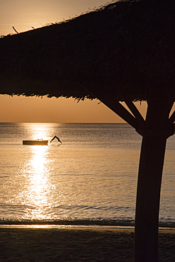 Silhouette of thatched parasol and young woman jumping from bathing platform into the water in front of Ong Lang Beach, Ong Lang, Phu Quoc Island, Kien Giang, Vietnam, Asia
