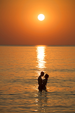 Silhouette of a romantic young couple in the water in front of Ong Lang Beach at sunset, Ong Lang, Phu Quoc Island, Kien Giang, Vietnam, Asia