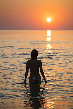 Silhouette of young woman in the water in front of Ong Lang Beach at sunset, Ong Lang, Phu Quoc Island, Kien Giang, Vietnam, Asia