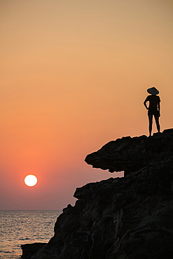 Silhouette of young woman wearing conical hat and looking out to sea from rock ledge next to Dinh Cao Shrine at sunset, Duong Dong, Phu Quoc Island, Kien Giang, Vietnam, Asia