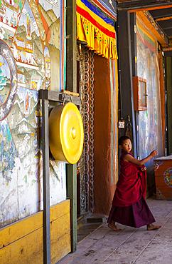 A boy monk, dressed in bright colors, shot inside a Bhutanese monistary. Bhutan.