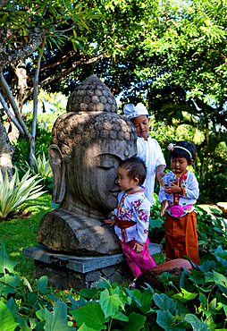3 Balinese children playing in tradintional clothes around a huge Buddha statue, in a tropical setting.