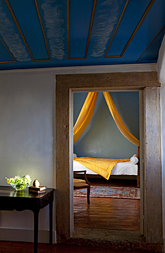 A peek into a room, with a bed, mounted with a bright, yellow canape. Shot inside Palacio Belmont, in Lisbon, Portugal.