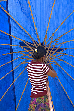 A balines woman in a striped blouse, opening a bright, blue umbrella in the market. Singaraja, Bali.