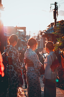 Women in the evening sun dressed in kimonos Kyoto, Japan