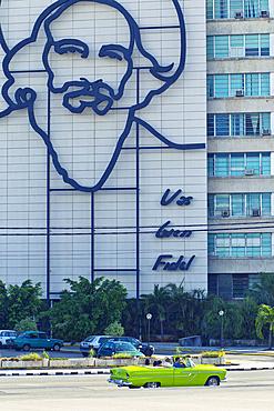 Building with image of Fidel Castro and classic car on Plaza de La Revolución in Havana, Cuba