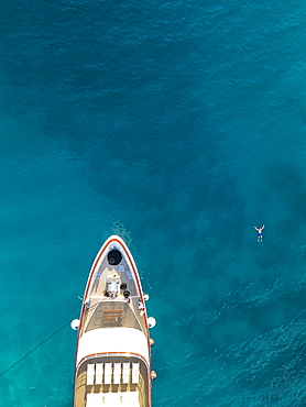 Aerial view of cruise ship with man who swims next to the bow in the water, near Kampor, Primorje-Gorski Kotar, Croatia, Europe