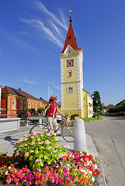 Woman with bicycle near a church, Wallsee-Sindelburg, Mostviertel, Lower Austria, Austria