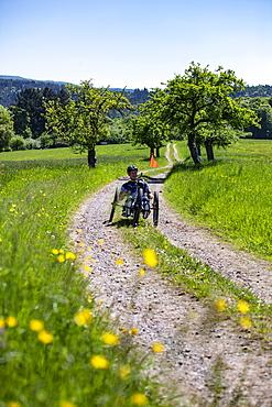 Man rides a bicycle for paraplegics on a dirt road through lush spring meadow, Heimbuchenthal, Räuberland, Spessart-Mainland, Franconia, Bavaria, Germany, Europe