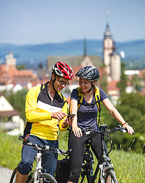 Young man and young woman on mountain bikes use smartphones for navigation, Tauberbischofsheim, Baden-Wuerttemberg, Germany, Europe