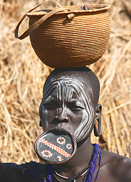 Ethiopia; Southern Nations Region; southern Ethiopian highlands; Mago National Park; lower Omo River; young Mursi woman with traditional lip dish and face-painting; Terracotta lip plate with painted and incised patterns