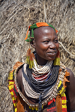 Ethiopia; Southern Nations Region; Kolcho village; on the Omo River; Omo Valley; Woman from the ethnic group of the Karo; dressed in a typical leather apron; Head and neck jewelry made from multicolored pearl necklaces