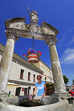 Woman filling bottle at fountain, Poechlarn, Lower Austria, Austria