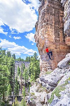 "Man rock climbing at ""The Pit"" in Sandy's Canyon, Flagstaff, Arizona, USA"