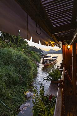 Side of river cruise ship Mekong Sun on river Mekong and longtail boat at dusk, Luang Prabang, Luang Prabang Province, Laos, Asia
