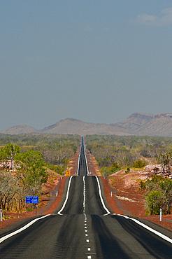 The highway runs lonely in the heat through the outback, Kununurra, Western Australia, Australia