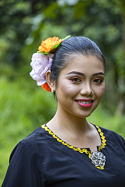 Portrait of a cheerful young woman in traditional costume in the Sarawak Cultural Village, near Kuching, Sarawak, Borneo, Malaysia, Asia