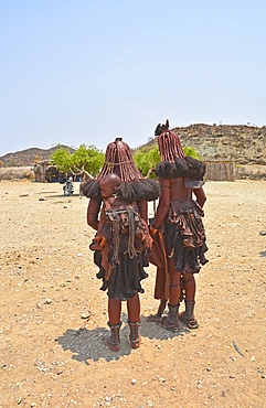 Angola; in the southern part of Namibe Province; two Muhimba women with their children; dressed in leather aprons; traditional hair styling