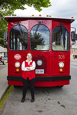 Woman driver stands in front of red tourist bus, Kingston, Ontario, Canada, North America