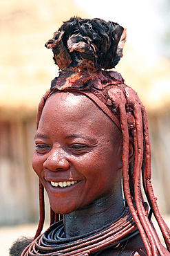 Angola; southern part of Namibe Province; Muhimba woman with traditional hair styling; Strands of hair stuck together with red earth and fluffy fur