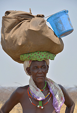Angola; in the western part of the province of Cunene; Woman on the street; with luggage on his head