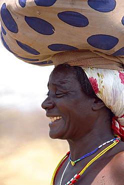 Angola; western part of the province of Cunene; Woman with luggage on her head; on the road