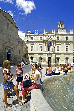 Young women at a fountain in front of the town hall, Place de la Republique, Arles, Bouches-du-Rhone, Provence, France, Europe
