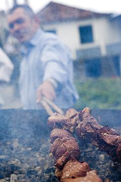 Man grilling Espetada beef skewer kebabs at a religious festival, Ponta Delgada, Madeira, Portugal