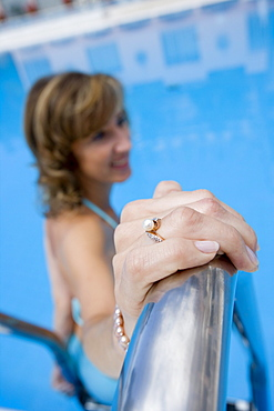 Ring on hand of woman in swimming pool at Reid's Palace Hotel, Funchal, Madeira, Portugal