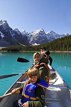 Family in paddle boat, Moraine Lake, Banff National Park, Alberta, Canada