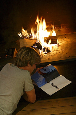 Young man reading in front of open fireplace