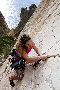 A young woman, a climber, a sportclimber, freeclimber, climbing at Ix-Xaqqa rock face, Malta, She protects with nuts and wires, Europe