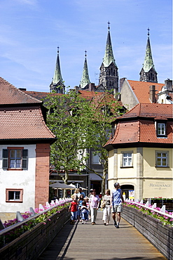 Pedestrians on a bridge overthe Regnitz river and the four steeples of the cathedral, Bamberg, Upper Franconia, Bavaria, Germany