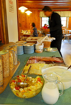 breakfast buffet with cereal and cold cuts, guests at tables out of focus in background, hut Franz-Senn-Huette, Stubaier Alpen range, Stubai, Tyrol, Austria