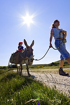 A donkey on a lead, Mother and daughter family-hiking with a donkey in the Cevennes mountains, France