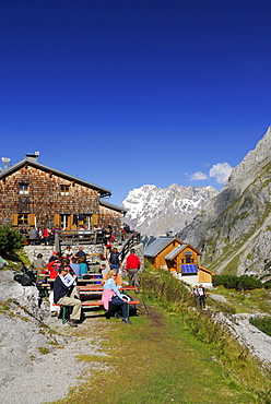 Hikers resting in front of hut Coburger Huette with view to Zugspitze range, Mieminger Gebirge range, Tyrol, Austria