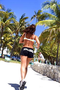Young woman jogging at Lummus Park under blue sky, South Beach, Miami Beach, Florida, USA