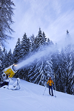 Woman skiing near snow cannon, Wiedersberger Horn, Kitzbuehel Alps, Tyrol, Austria