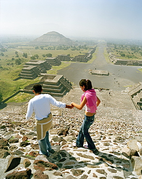 Young couple on top of moon pyramid, view at street of the dead, temple complex Teotihuacan, Mexico, America