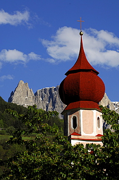 The steeple of Saint Oswald church between green branches and mountains, Kastelruth, South Tyrol, Italy, Europe