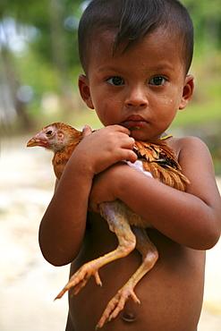 Sea gypsy, Moken boy carrying a chicken, Mergui Archipelago, Andaman Sea, Myanmar, Burma, Asia
