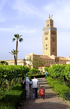 Family at a park in front of the Minaret of the Koutoubia Mosque, Marrakesh, South Morocco, Morocco, Africa