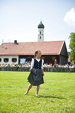 Girl (8-10 years) wearing dirndl standing on meadow, May Running, Antdorf, Upper Bavaria, Germany