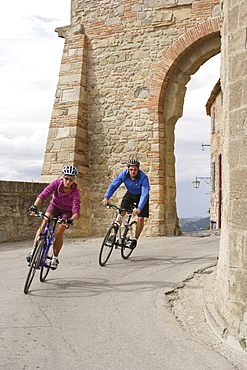 Young couple riding bicycles on a street at San Leo, Marche, Italy, Europe