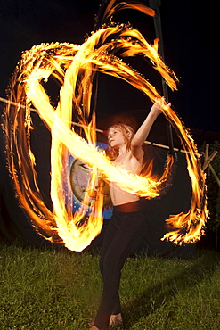 Boy juggling with fire at night, Austria
