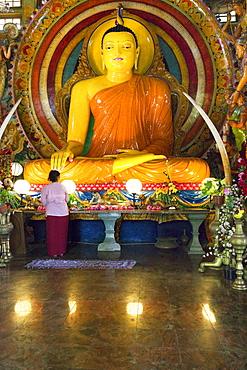 Woman in front of a big Buddha statue in the Gangaramaya temple, Colombo, Sri Lanka, Asia