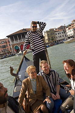 Gondolier on a gondola crossing Grand Canal with passengers, Venice, Veneto, Italy