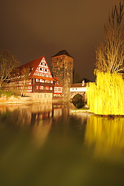 Illuminated Weinstadel, wine store and water tower and the river Pegnitz at night, Nuremberg, Bavaria, Germany