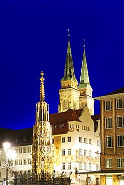 Illuminated fountain Schoener Brunnen on the market square and St. Sebaldus church at night, Nuremberg, Bavaria, Germany