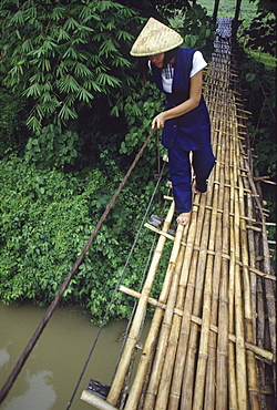 Woman crossing hanging bridge over Loboc River, Loboc, Bohol Island, Philippines, Asia